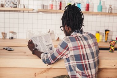 back view of african american man sitting at bar counter and reading business newspaper