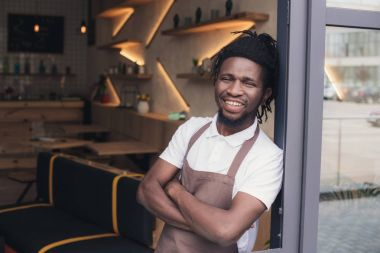 cheerful african american cafe owner in apron standing at entrance