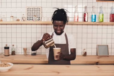 african american barista making coffee in disposable cup at bar counter