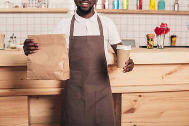 cropped view of african american barista holding disposable cup of coffee and kraft package at bar counter