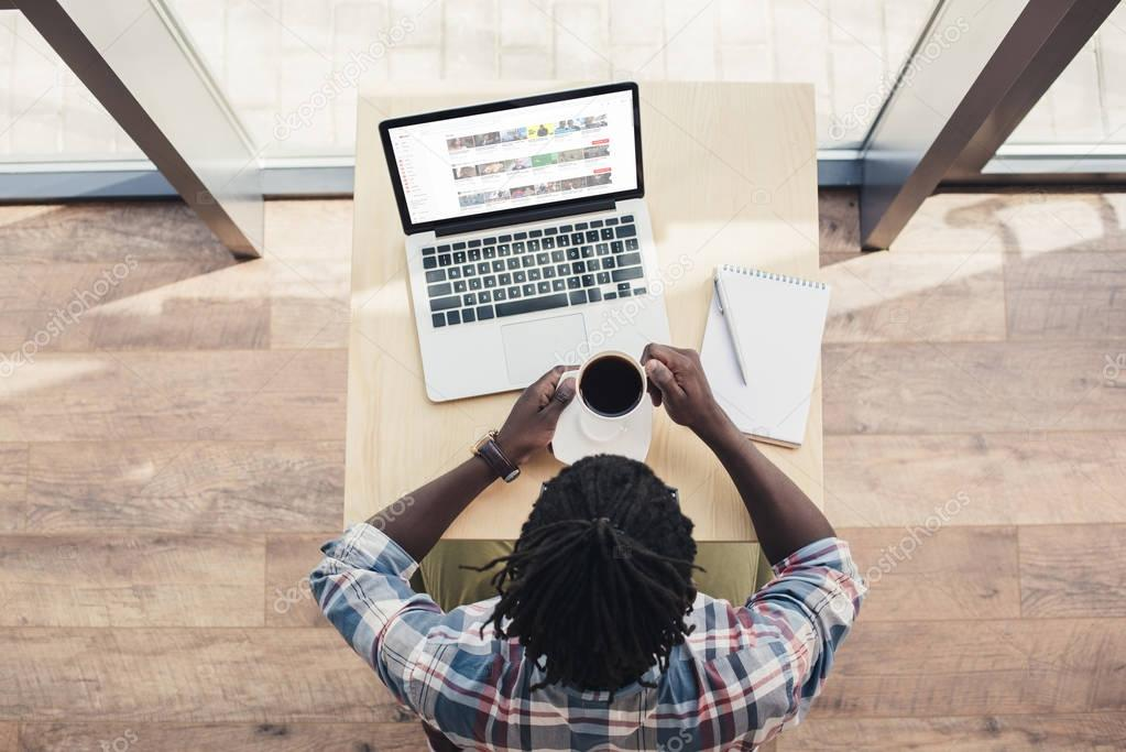 overhead view of african american man drinking coffee and using laptop with youtube website