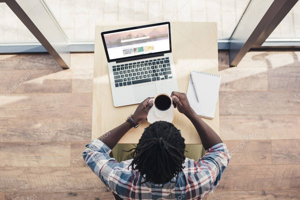 overhead view of african american man drinking coffee and using laptop with shutterstock website