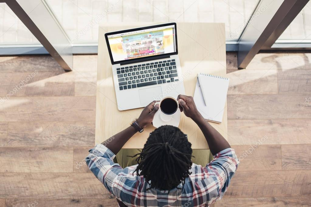 overhead view of african american man drinking coffee and using laptop with aliexpress website
