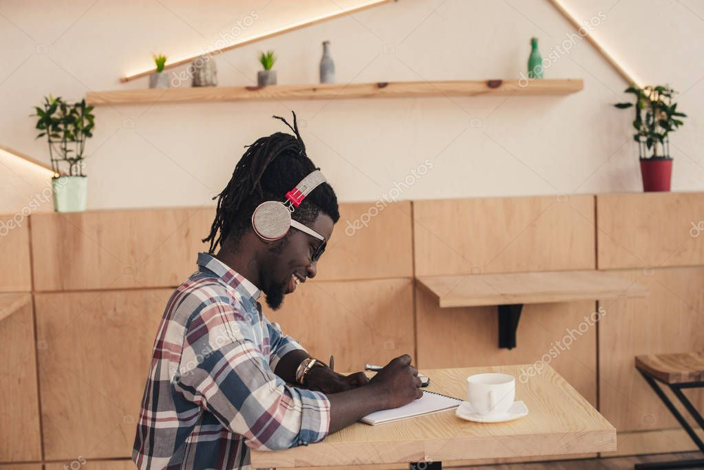 smiling african american man listening music and writing in notepad in coffee shop