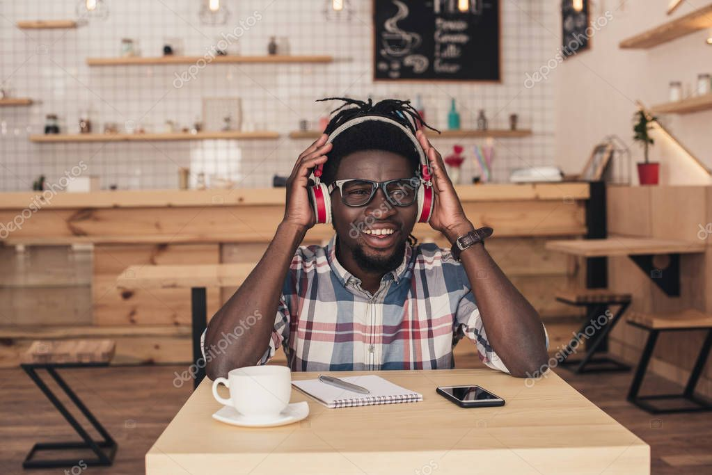 cheerful african american man listening music in coffee shop
