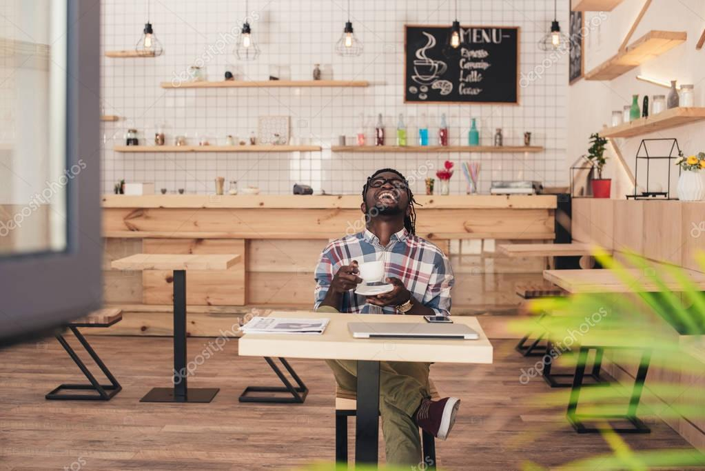 laughing african american man drinking coffee at table in cafe