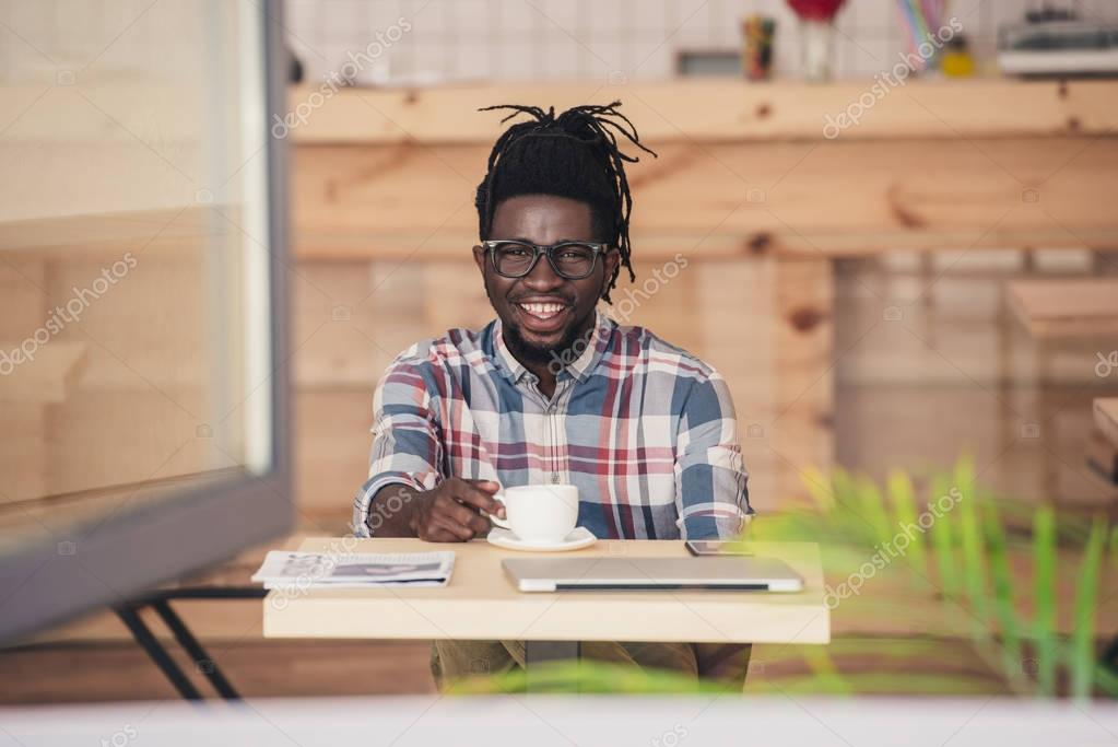 cheerful african american man drinking coffee at table in cafe