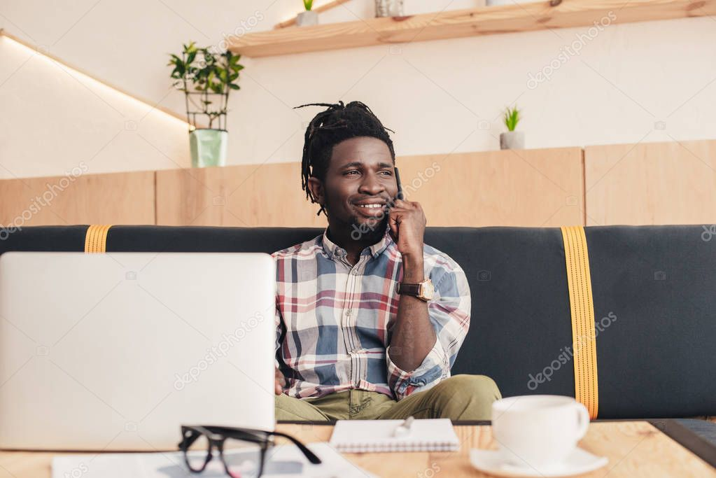 smiling african american man using smartphone and laptop in coffee shop