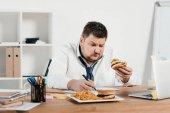 übergewichtiger Geschäftsmann bei der Arbeit, während er im Büro Hamburger und Pommes frites isst