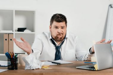 confused overweight businessman sitting at workspace with documents and laptop
