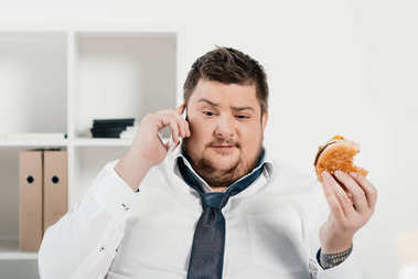 overweight businessman talking on smartphone while eating hamburger in office