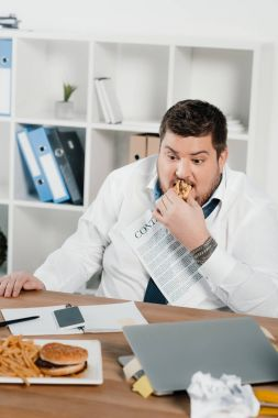 fat businessman eating hamburgers and french fries in office