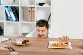 fetter Geschäftsmann, der Donuts oder Hamburger mit Pommes zum Mittagessen auswählt