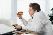 overweight businessman eating hamburger while working in office