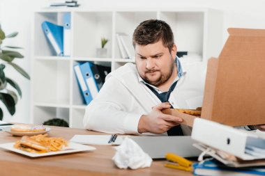 fat businessman with pizza looking at junk food at workplace