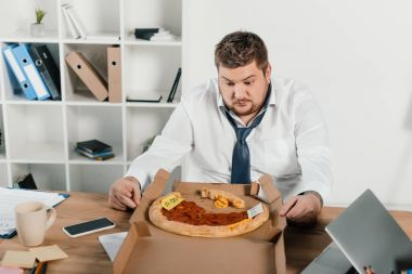 overweight businessman looking at pizza while sitting in office
