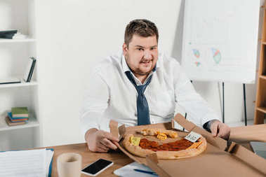 overweight businessman eating pizza at workplace in office