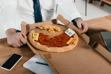 cropped view of overweight businessman eating pizza at workplace