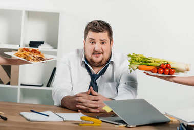 overweight businessman choosing healthy or junk food at workplace in office