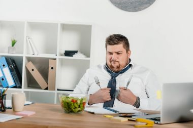 confused overweight businessman with fork and knife looking at fresh salad