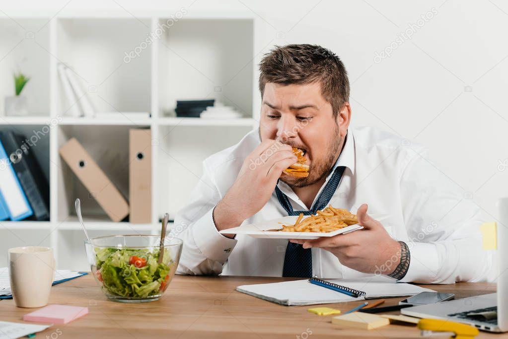 overweight businessman eating hamburger while looking at salad