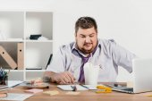 overweight businessman eating noodles at workplace in office