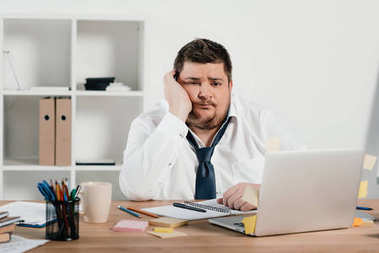 bored overweight businessman working with notepad and laptop in office
