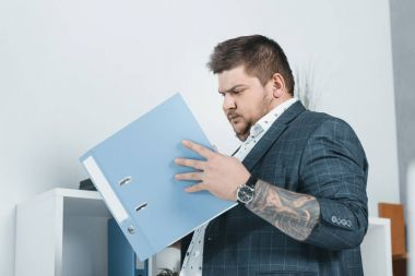 overweight businessman in suit working with documents in folders