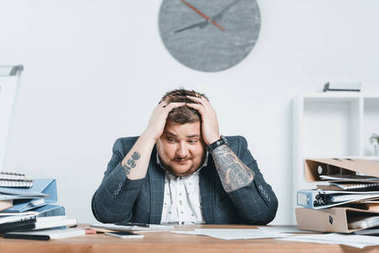 stressed overweight businessman in suit working with documents in office