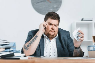 overweight businessman in suit talking on smartphone and working with documents in office