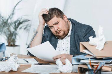 Fat businessman in suit doing paperwork in office stock vector