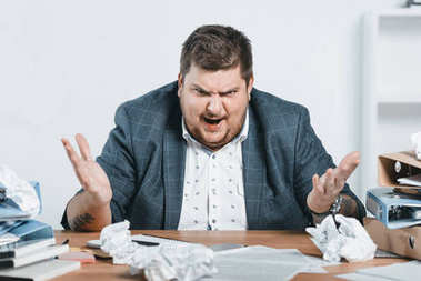 Angry overweight businessman in suit working with documents in office stock vector