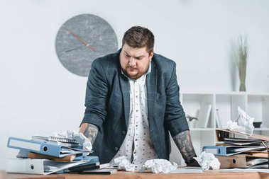 overweight businessman in suit doing paperwork in office