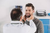 male doctor palpating male patient lymph nodes