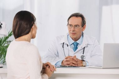 male doctor and female patient sitting at talking at clinic