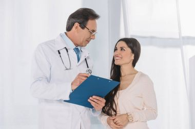 smiling doctor and patient looking at each other