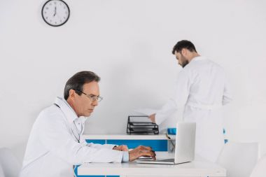 mature and young adult doctors at clinic