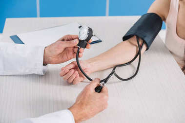 cropped image of doctor measuring female patient pressure