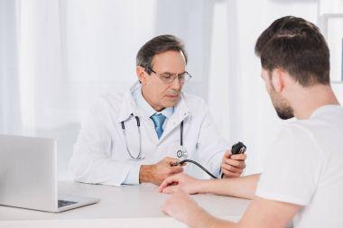 doctor measuring male patient pressure