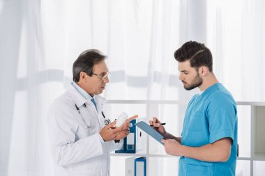 doctor holding pills and talking to nurse