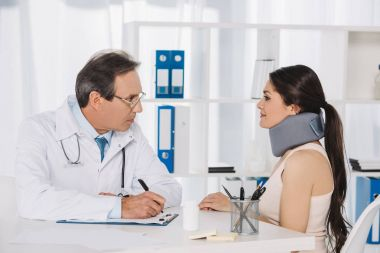 doctor sitting and talking with female patient in neck brace