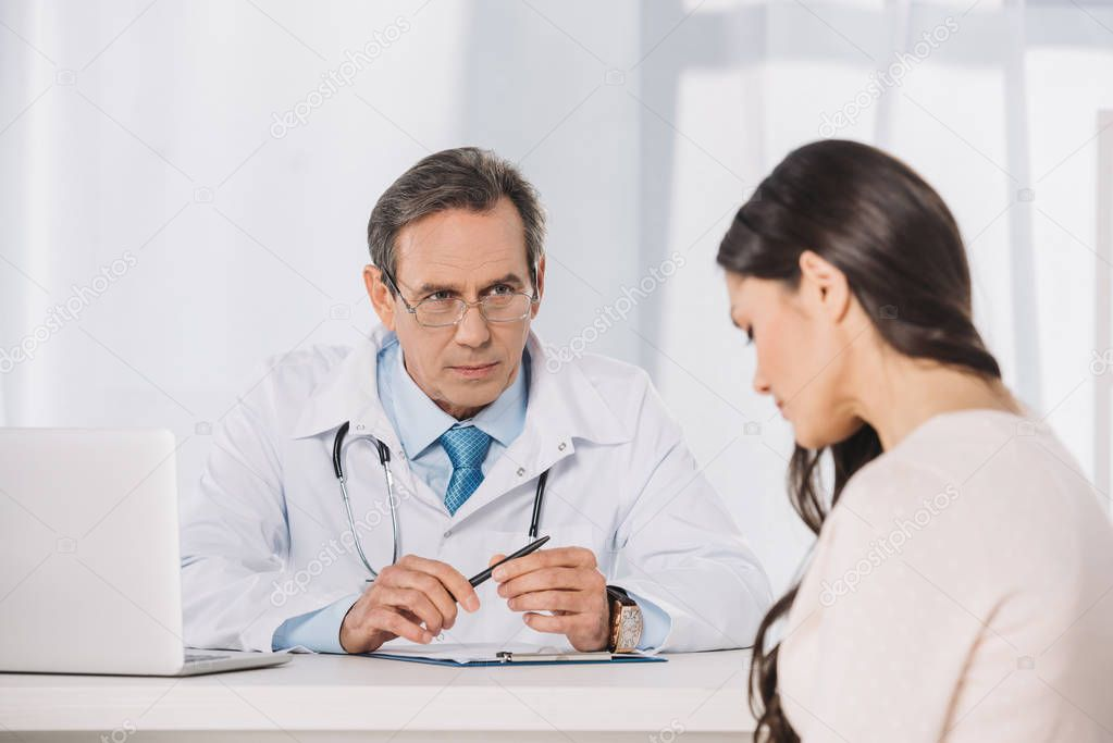 male serious doctor and female patient sitting at talking at clinic