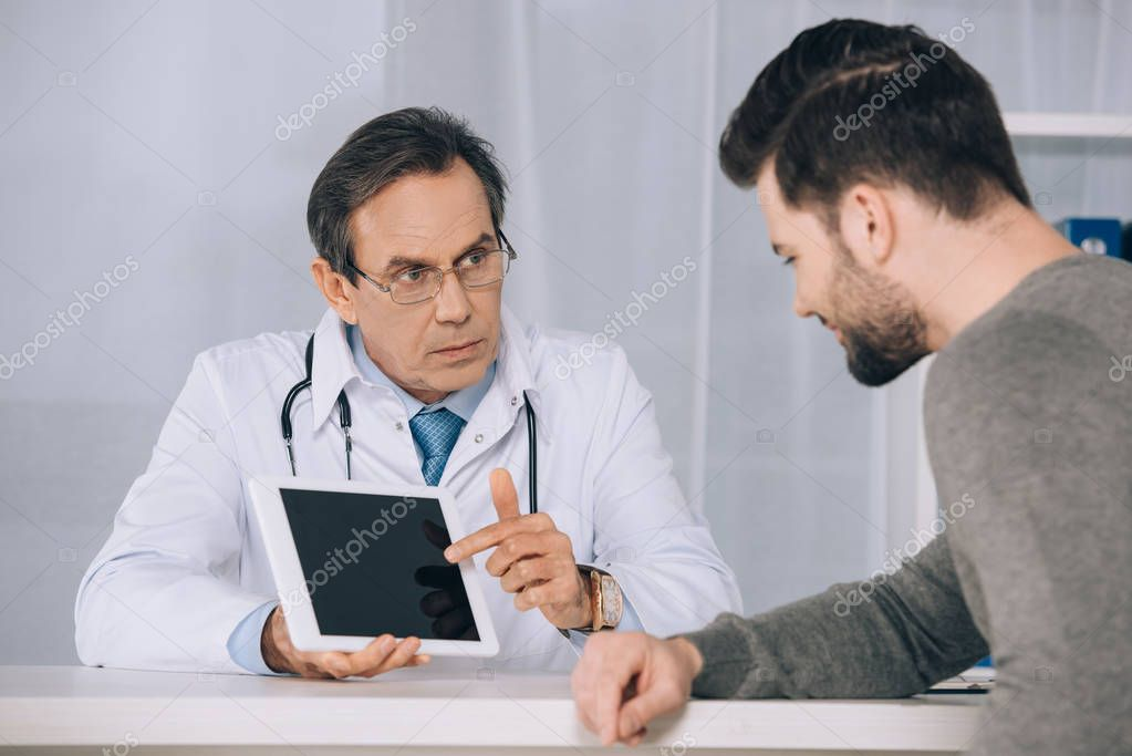 doctor showing something to patient on tablet