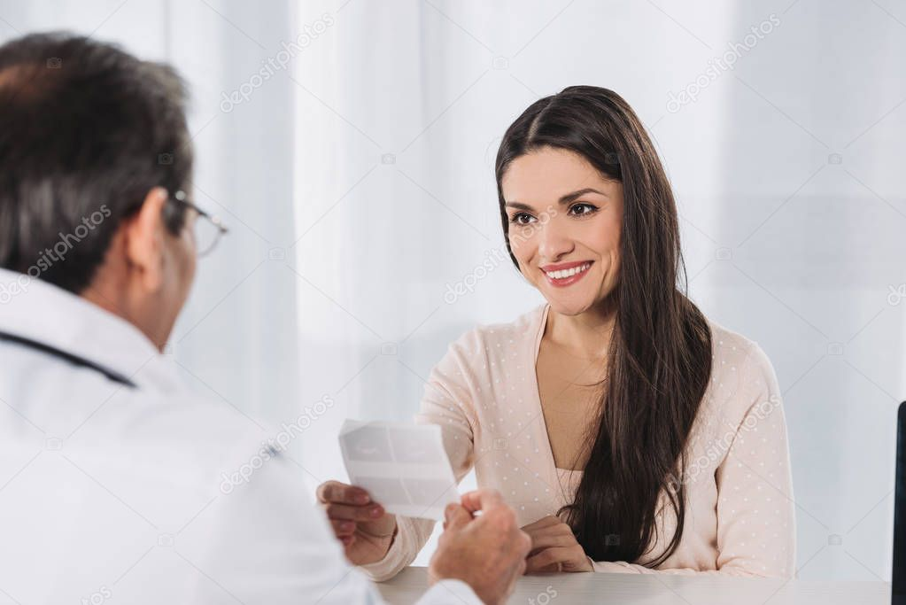cropped image of doctor giving photo of ultrasound diagnostics to happy woman