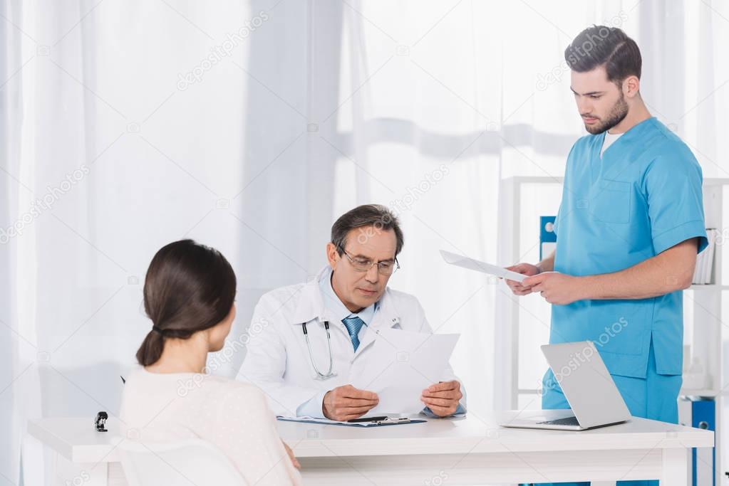doctor reading female patient documents at clinic