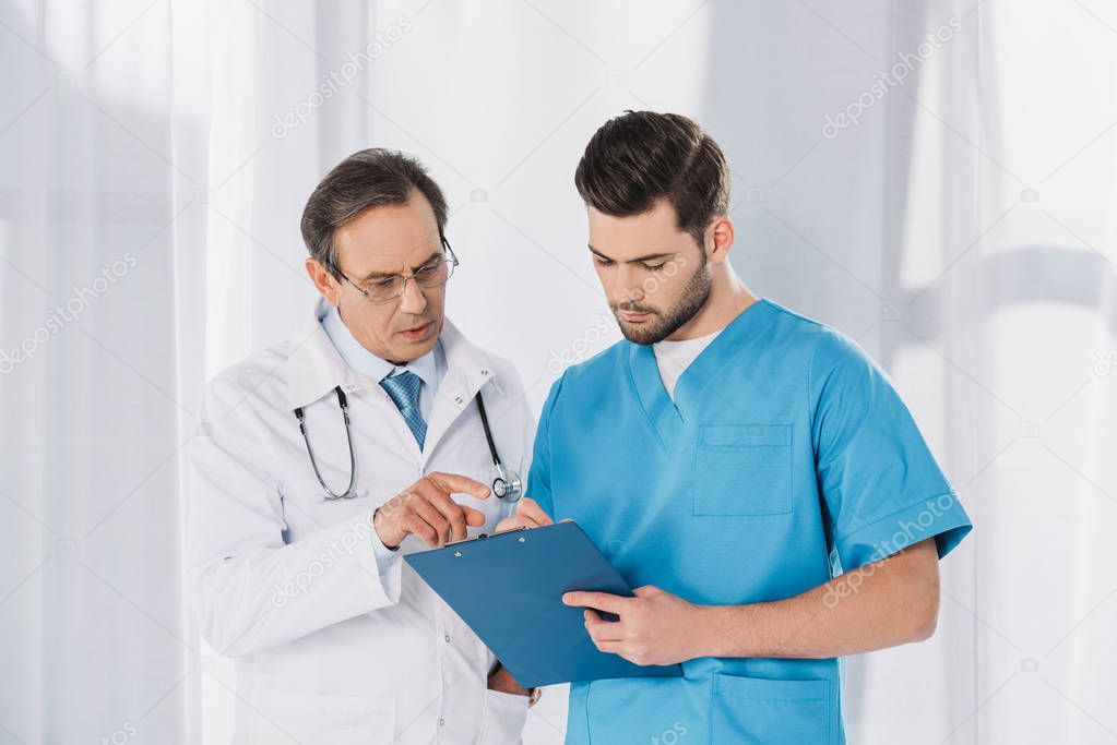 male doctor and nurse looking at clipboard
