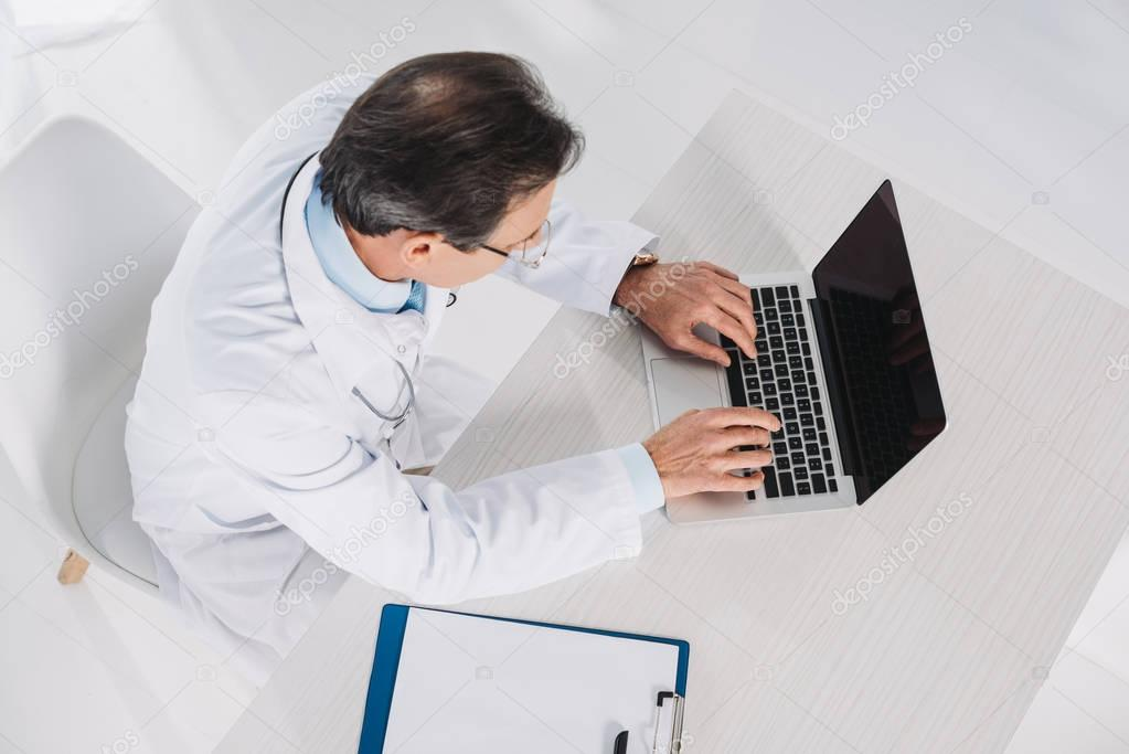 overhead view of doctor using laptop at working place
