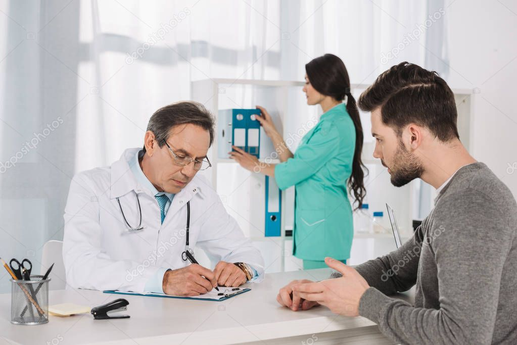 male patient talking to doctor at clinic