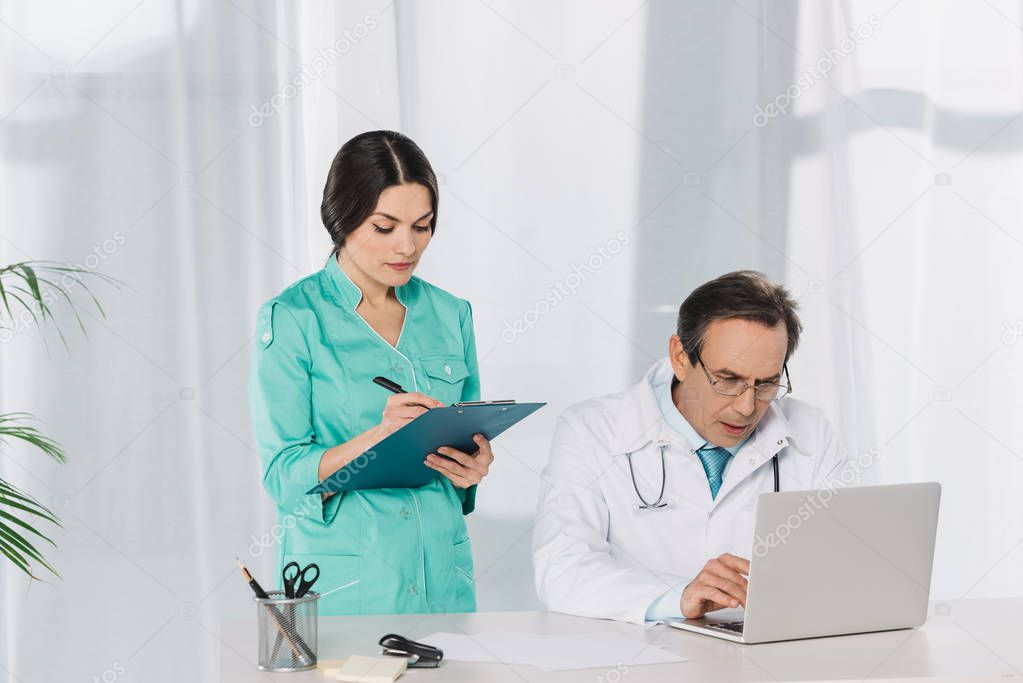 nurse writing to clipboard and doctor using laptop