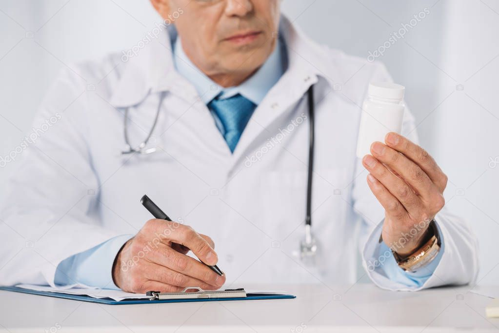 cropped image of doctor looking at pills